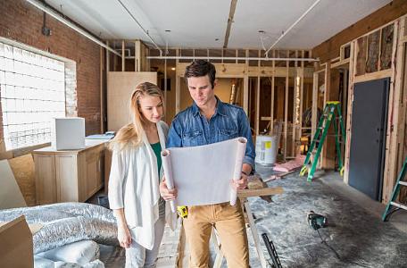 deux personnes regardent des plans dans une maison en construction