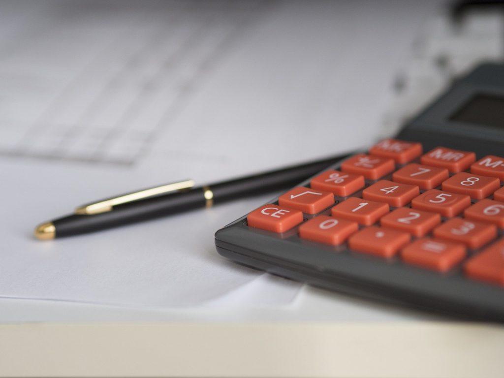 Calculatrice et stylos posés sur un avis d'imposition