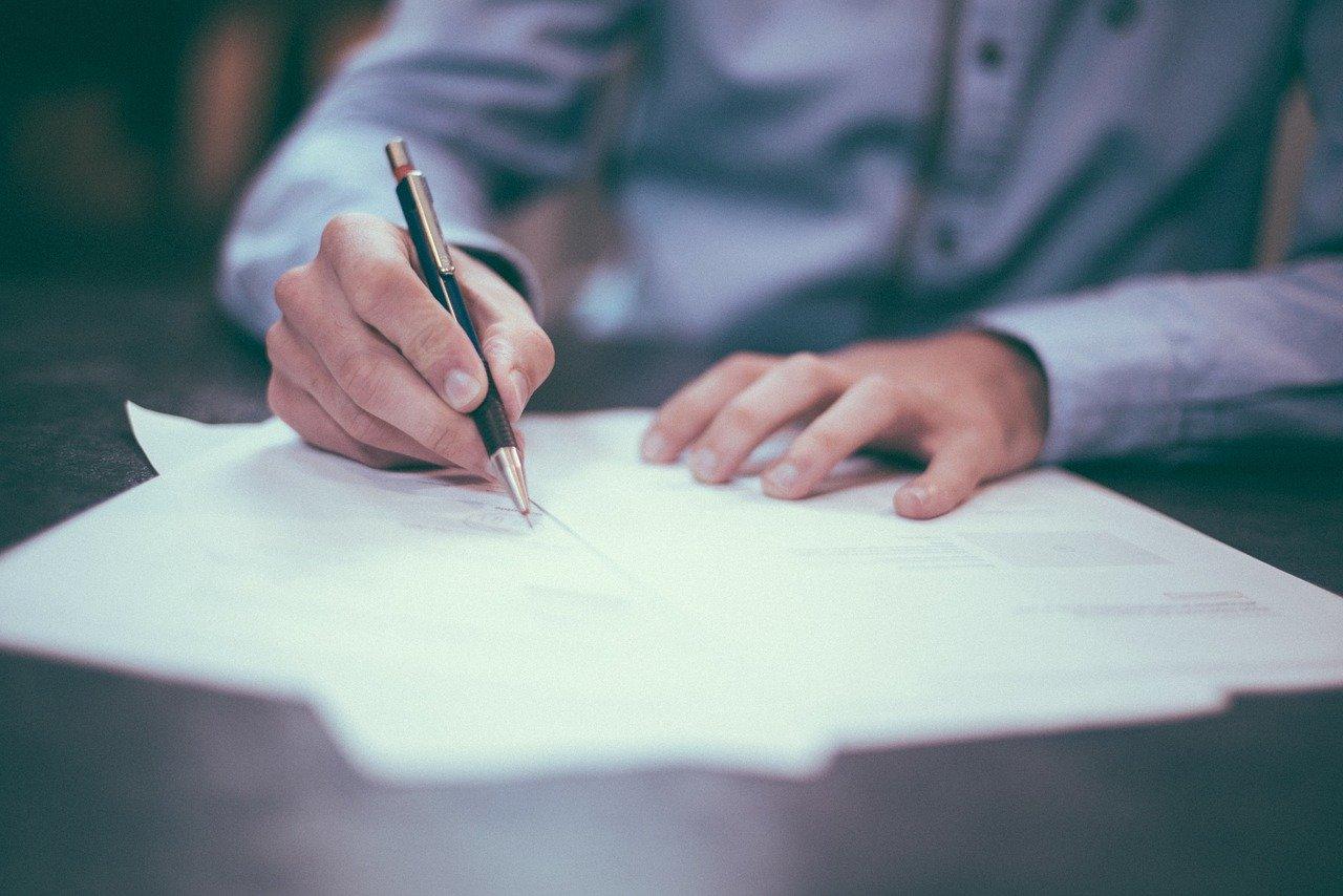 homme écrivant une lettre sur du papier avec un stylo