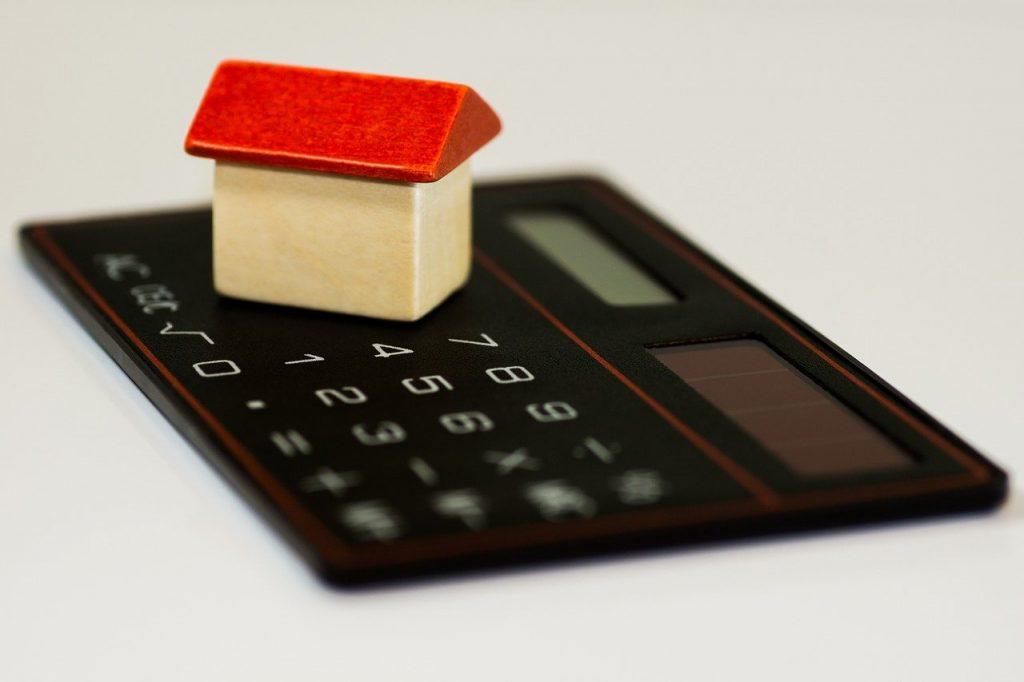 maison miniature posée sur un calculatrice