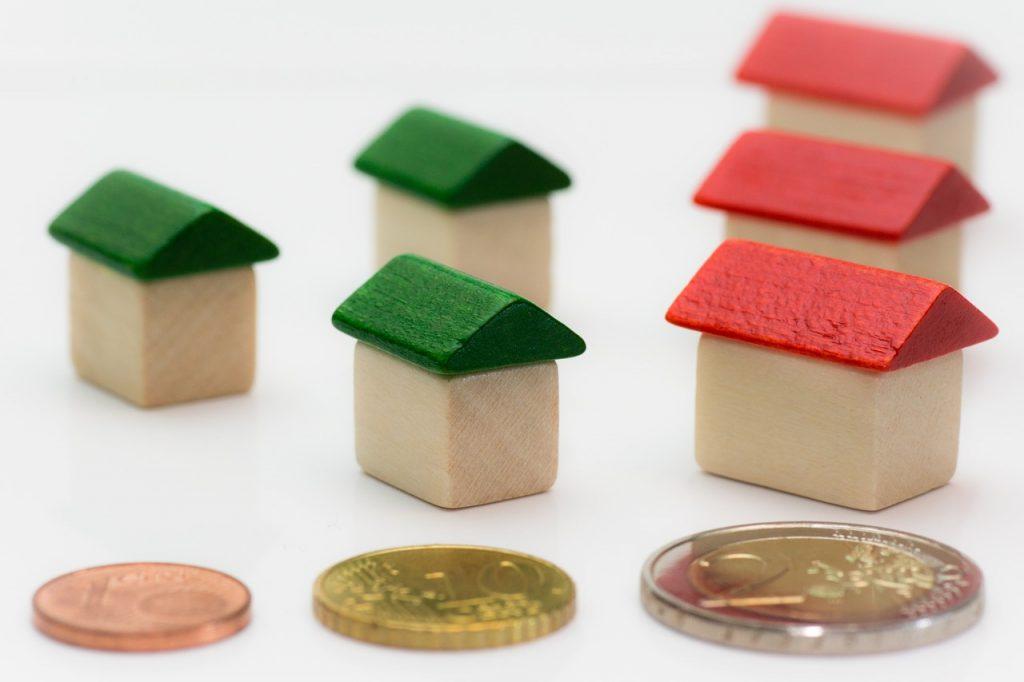petites maisons en bois devant des pièces de monnaie